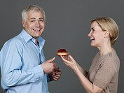 Mature couple with cake, smiling