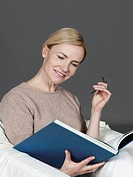 Mature woman reading book, smiling