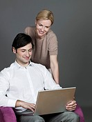 Man and woman using laptop, smiling