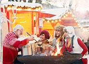 Austria, Salzburg, Senior man serving drink to young people at christmas market, smiling