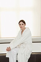 Germany, Berlin, Mature woman sitting on bathtub, portrait