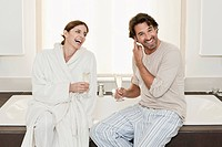 Germany, Berlin, Mature couple sitting on bathtub with sparkling wine
