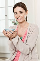 Germany, Berlin, Mature woman holding bowl, smiling, portrait (thumbnail)