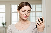 Germany, Berlin, Mature woman looking at mobile phone