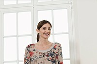 Germany, Berlin, Mature woman smiling in front of window, portrait