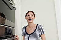 Germany, Berlin, Mature woman looking by oven in kitchen, smiling