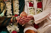 Mid section of bride and groom holding coconut together