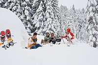 Austria, Salzburg, Men and women sitting at fire place in winter (thumbnail)