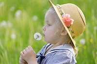Germany, Bavaria, Girl holding dandelion seed