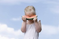 Germany, Bavaria, Girl eating piece of watermelon