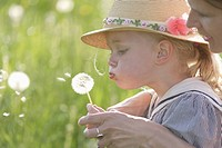 Germany, Bavaria, Mother and daughter blowing dandelion seed head, close up