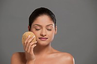 Close_up of young woman using massage sponge over grey background