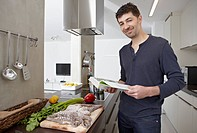 Germany, Cologne, Mid adult man with cook book in kitchen, portrait