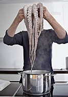 Germany, Cologne, Mid adult man cooking octopus in kitchen