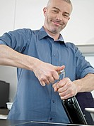Germany, Cologne, Mature man opening wine bottle, smiling, portrait