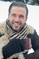 Austria, Salzburg County, Mature man with tea cup in snow, smiling, portrait