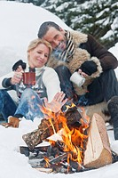 Austria, Salzburg County, Couple sitting near fireplace, smiling (thumbnail)