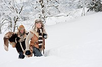 Austria, Salzburg County, Couple walking through winter landscape, smiling (thumbnail)