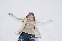 Austria, Salzburg County, Mid adult woman lying on snow, smiling