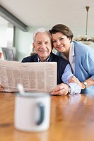 Germany, Leipzig, Senior man and woman with newspaper, smiling, portrait