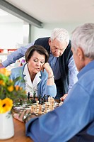 Germany, Leipzig, Senior men and woman playing chess