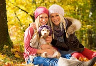 Austria, Sisters sitting with dog in autumn, smiling, portrait