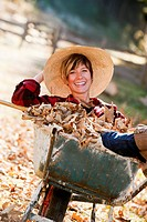 Austria, Salzburg County, Young woman in wheel barrow with autumn leaves, smiling