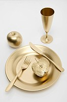Golden cutlery with apple on white background