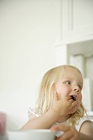 Germany, Bavaria, Girl eating with her hand