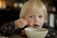 Germany, Bavaria, Girl eating from bowl