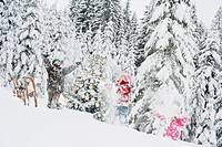 Austria, Salzburg County, Boy and girl having fun with christmas tree in snow