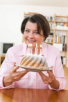 Germany, Leipzig, Senior woman holding birthday cake