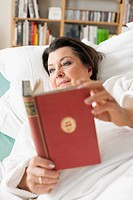 Germany, Leipzig, Senior woman lying on medical bed, reading book