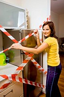 Young woman trying to open the fridge.