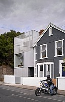 Private Residence Grangegorman, Dublin 7, Ireland. Architect ODOS Architects, 2009. View of front facade and adjoining house with owner on motorbike.
