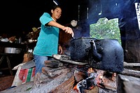 Young woman cooking over an open fire in the simple kitchen of farm workers, Comunidad Arroyito, Departamento Concepcion, Paraguay, South America