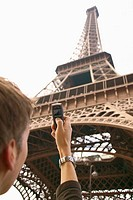 Man Photographing Eiffel Tower with Camera Phone