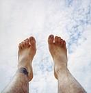 Feet before cloudy sky