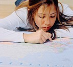 Teenage Girl Lying on Floor and Looking at World Map