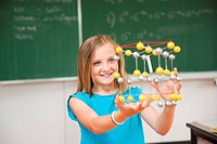Schoolgirl in a classroom with a model of an atom