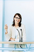 Smiling Businesswoman with Glasses Standing at Podium
