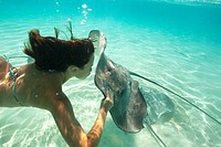 girl kissing stingray underwater
