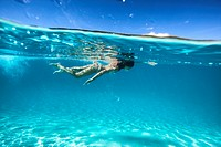 young woman swimming in turquoise lagoon shot underwater