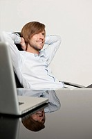 Content businessman at desk leaning back