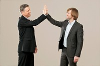 Two happy businessmen high fiving