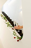 Hands holding champagne glasses on staircase decorated with red roses