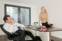 Businessman and businesswoman in office smiling at each other (thumbnail)