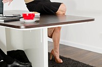 Woman sitting on desk with cup of coffee