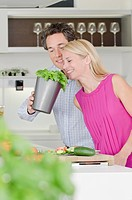 Couple in kitchen smelling at basil