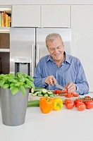 Senor man slicing vegetables in kitchen